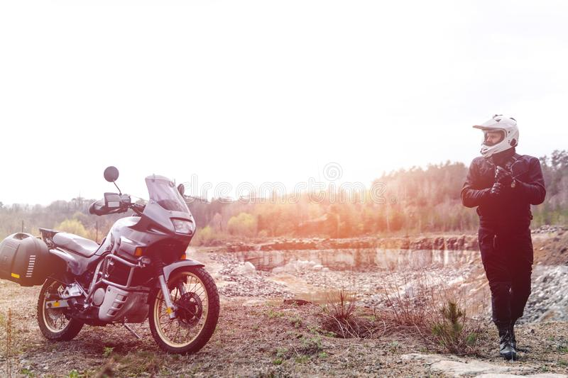Motorcyclist man stands with his Adventure Motorbike. Off road. Motorcycle trip. enduro Traveling, Lifestyle Travel dual sport. Outdoor concept. clothing with stock photography