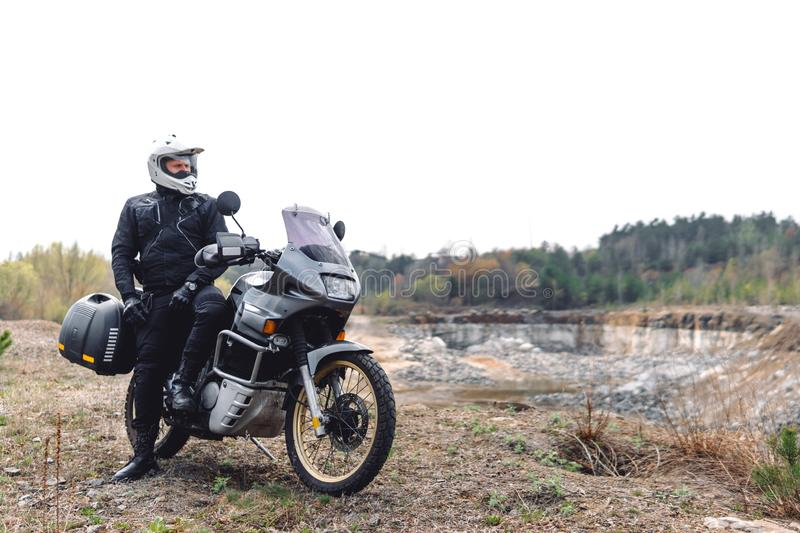 Motorcyclist man stands with his Adventure Motorbike. Off road. Motorcycle trip. enduro Traveling, Lifestyle Travel dual sport. Outdoor concept. clothing with royalty free stock photo