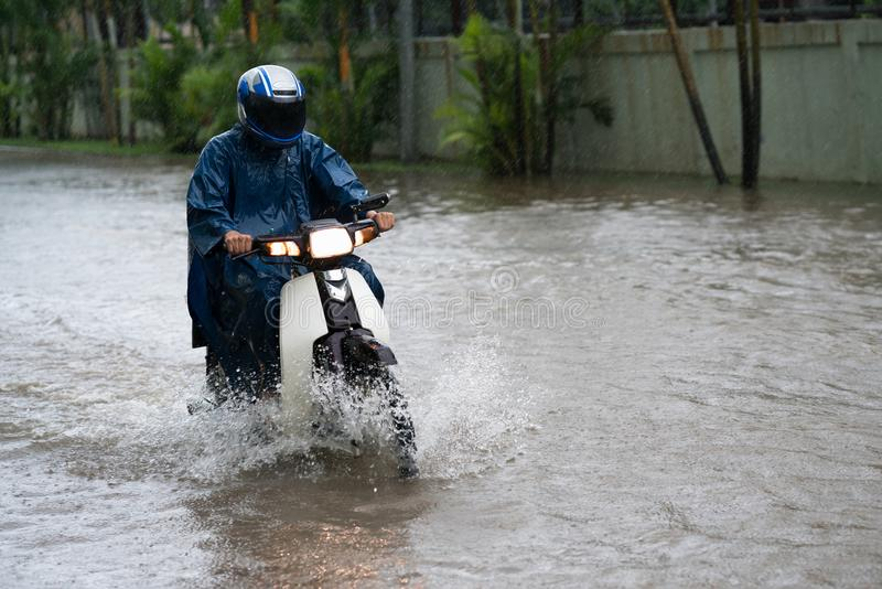 A motorcyclist rides along a flooded street in Hanoi city, Vietnam royalty free stock image