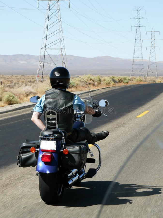 Motorcyclist rides one-handed through the desert stock images