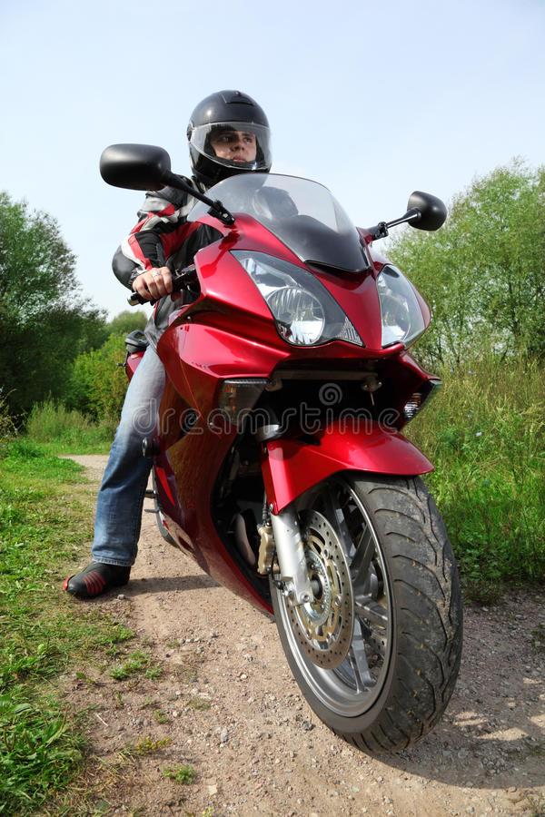 Motorcyclist standing on country road stock photography