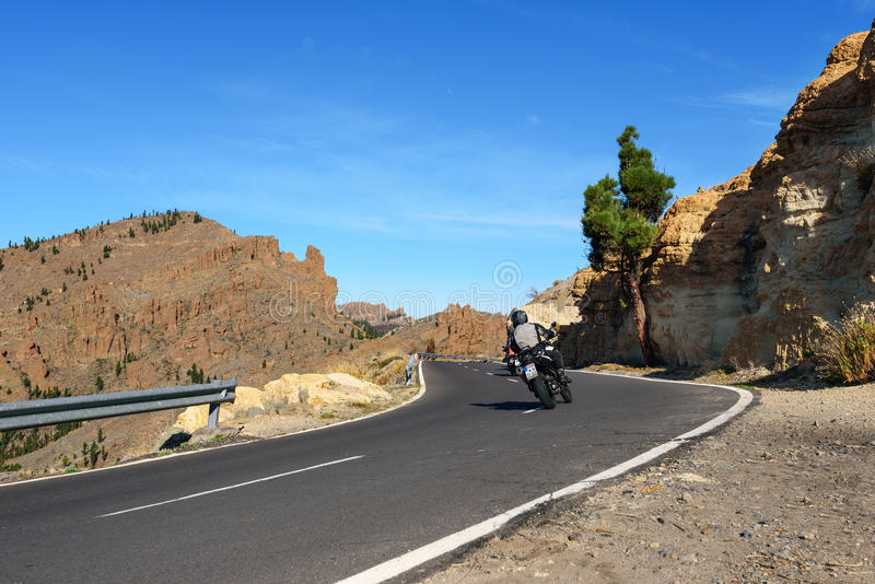 Motorcyclists driving on road through mountains at Teide national park on Tenerife island, Spain. TENERIFE, SPAIN - DECEMBER 2015: Motorcyclists driving on road stock photos