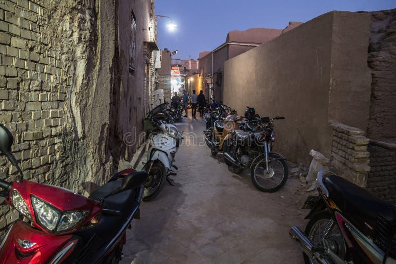 Motorcycyles parkte in einer typischen Straße der alten Stadt von Yazd, der Iran, nachts mit seinen typischen Lehmwänden u. -gebä stockbild