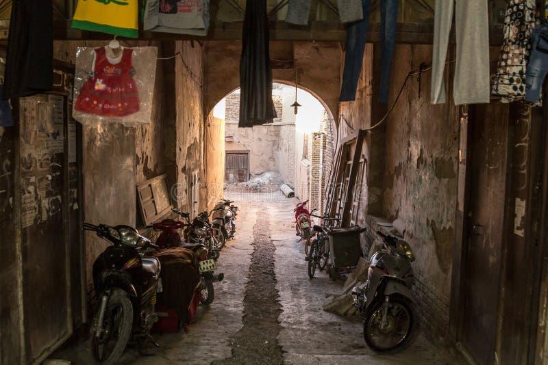 Motorcycyles, sparkcyklar, mopeder och cyklar som parkeras i en typisk gata av den gamla staden av Yazd royaltyfri foto