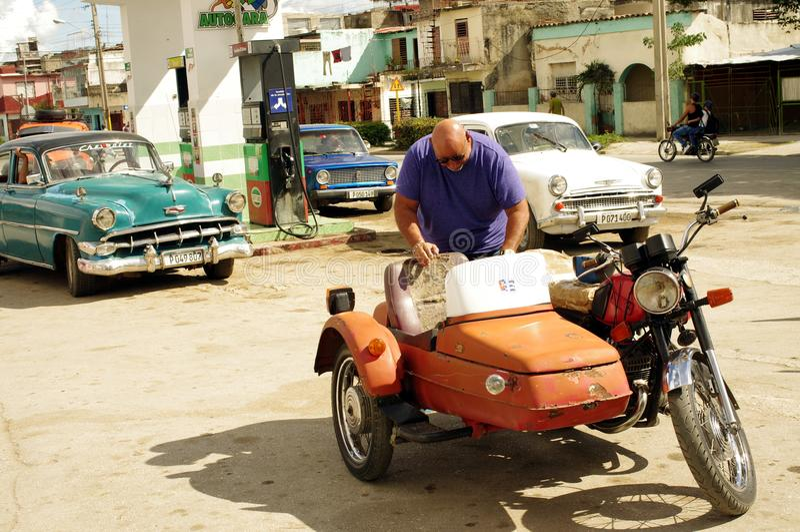 Motorcykel med en sidecar på bensinstationen i Kuba royaltyfria bilder