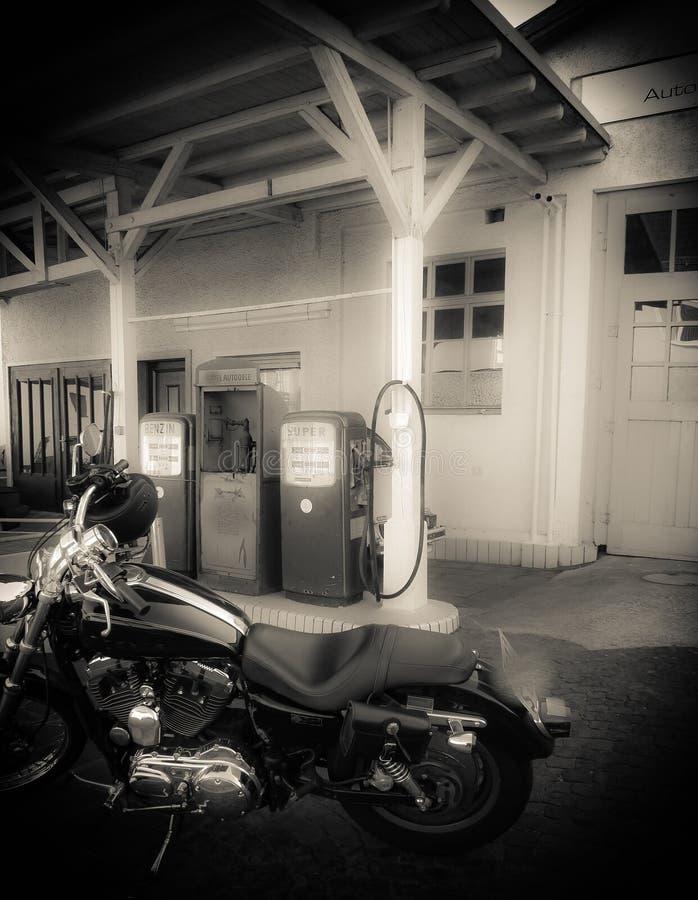 Motorcykel som är främst av gammal bensinstation royaltyfria bilder