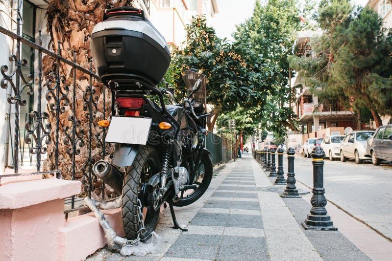 Motorcykeln parkeras på gatan och stängs till ett specialt lås mot stöld Säkerhet och förhindrande av brottet royaltyfri fotografi