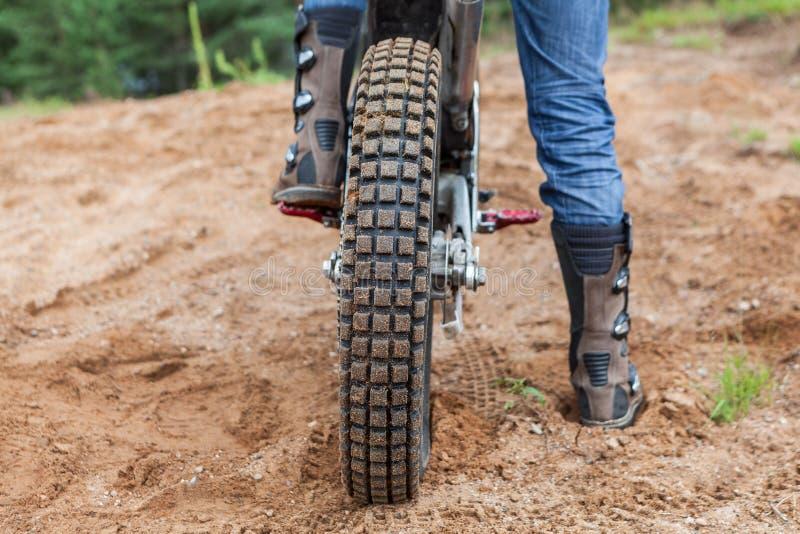 Motorcykelryttaren har en ritt i sandgrop, bakre sikt av cykelgummihjulet och mankängor royaltyfri bild