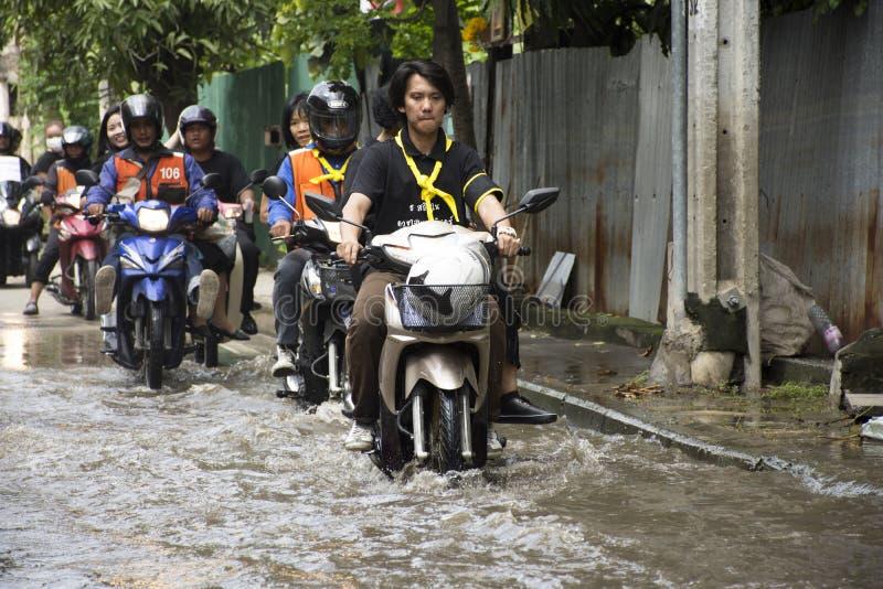 Motorcykeltaxi och den bärande folk passerade floden för volontär på vägen går att banka paitemplet royaltyfri bild