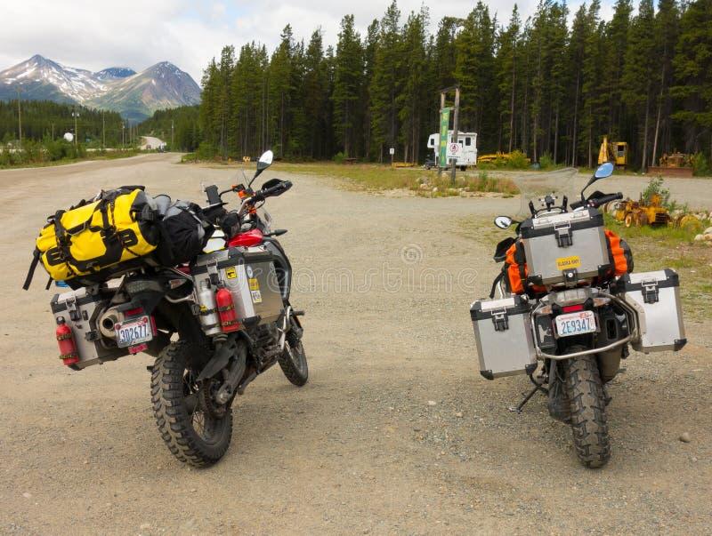 Motorcyklar väller fram utrustat för en vägtur som parkeras på ett vilaområde i nordliga Kanada arkivfoton
