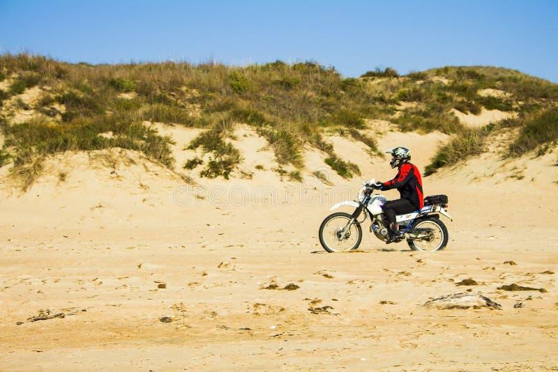 Motorcyklisten rider på sanden på stranden Ryssland, Blagoveshenskaya, 9 oktober 2108 royaltyfri bild