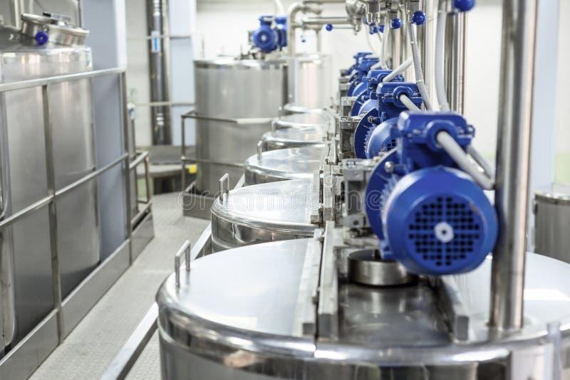 Motores eléctricos en los tanques de acero para los líquidos de mezcla, producción moderna de bebidas alcohólicas imagen de archivo