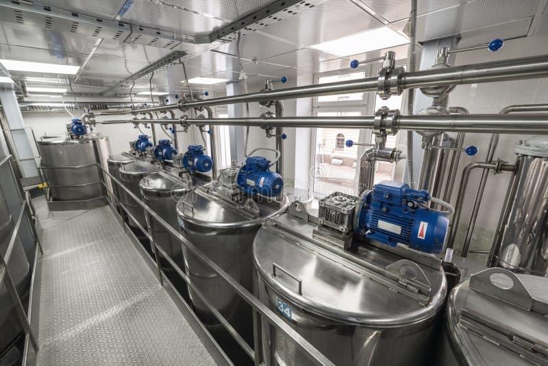 Motores eléctricos en los tanques de acero para los líquidos de mezcla, producción moderna de bebidas alcohólicas imagenes de archivo