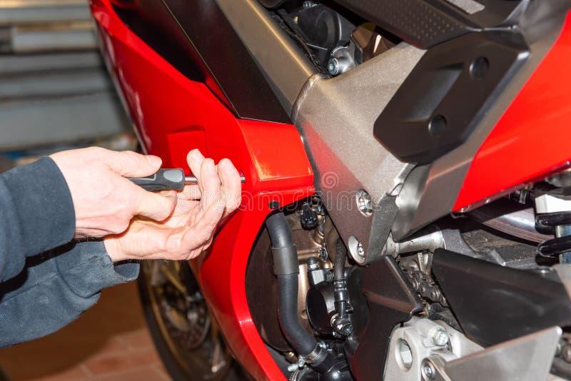 Motorfiets het mechanische schroeven op de stroomlijnkap van een motorfiets - Serie-Reparatieworkshop stock foto