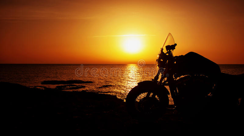 Motorfiets op zonsondergang stock afbeelding