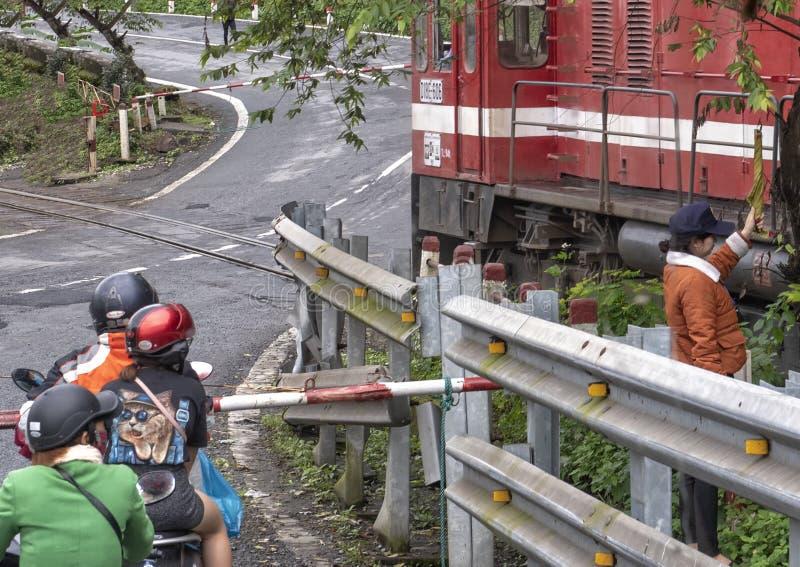 Motorfietsen met passagiers die op de trein wachten om over te gaan, Hai Van Pass, Vietnam stock fotografie