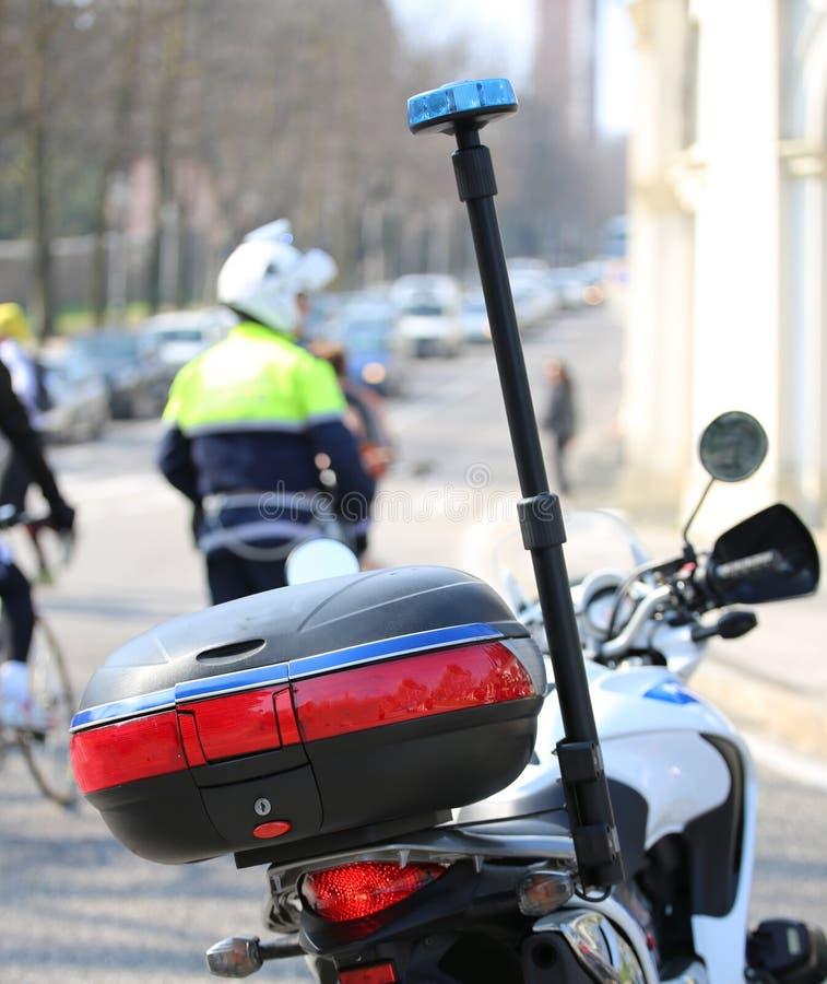motorfietspolitie met opvlammende sirene en een verkeersambtenaar op t stock fotografie