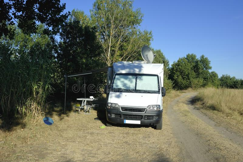 Motorhome die op een klein land wordt geparkeerd stock afbeelding