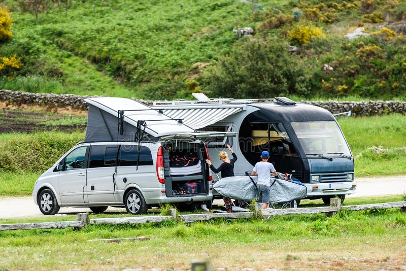 Motorhome RV and campervan are parked on a beach. Surfers on vacation are packing surfboards or boards after a day of wave surfing. Atlantic beach - Spain royalty free stock photos