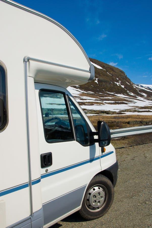 Motorhome/rv sur le côté de la route en Norvège avec les collines neigeuses à l'arrière-plan image libre de droits