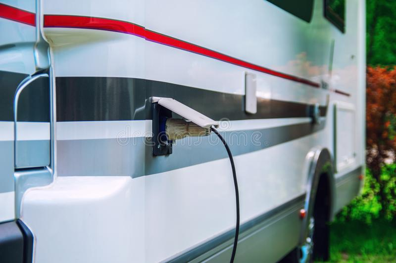 Motorhome stillife. Concept of power supply of the camper. Plug of the electric wire is inserted into the socket of the rv trailer.  royalty free stock image