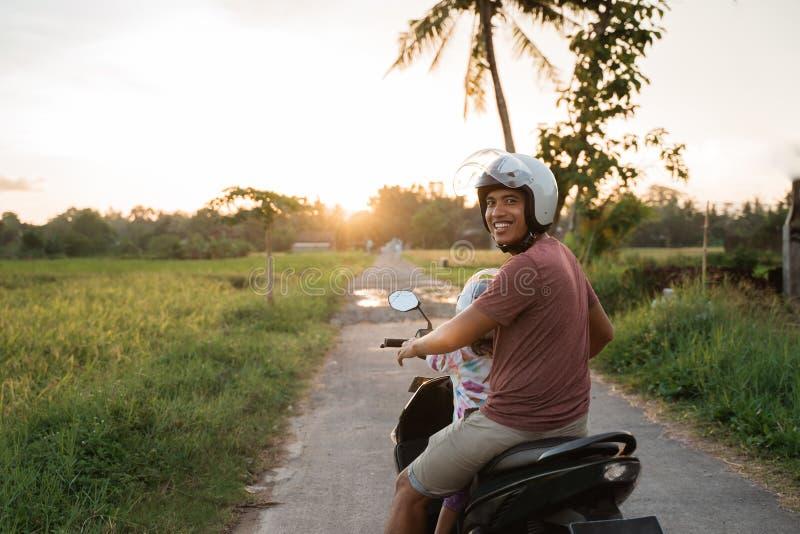 Motorino asiatico del motociclo di giro del bambino e del padre immagine stock libera da diritti