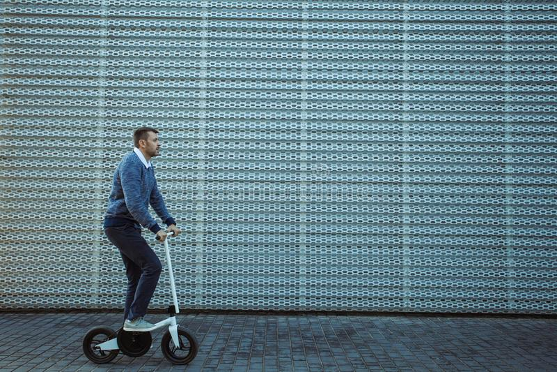 Motorino di guida dell'uomo davanti alla facciata moderna immagini stock