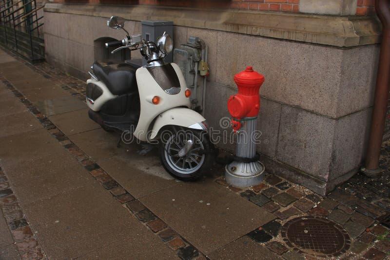 Motorino parcheggiato davanti ad una colonna del fuoco immagine stock libera da diritti