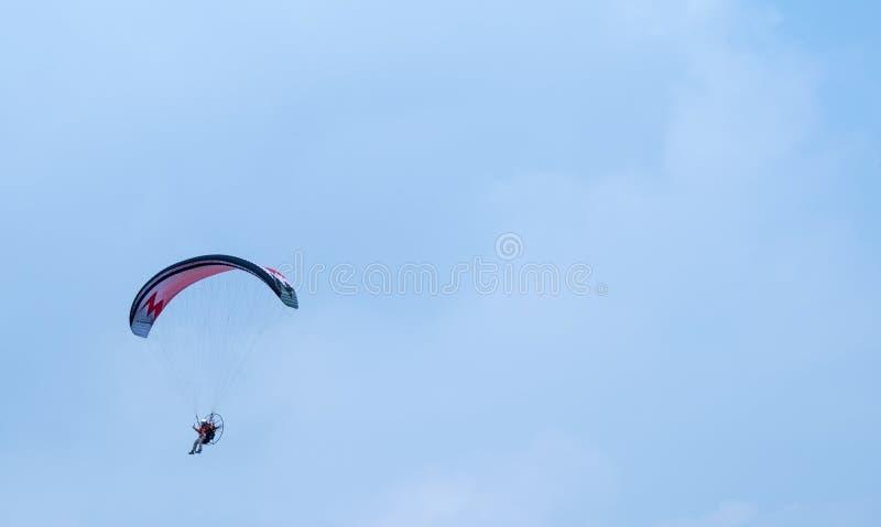Motoriserat paragliderflyg i himlen royaltyfri foto