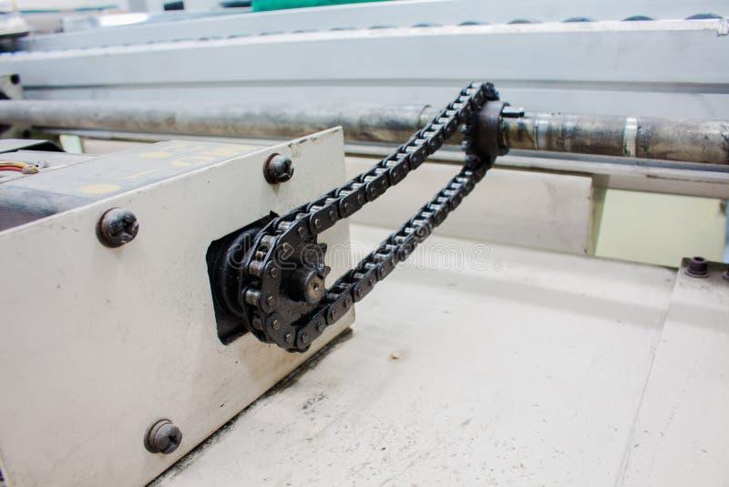 Motorisk axel för chain drev i transportörlinje arkivbilder