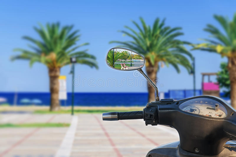 Motorisk cykelspegelreflexion med oskarp havsbakgrund royaltyfri bild
