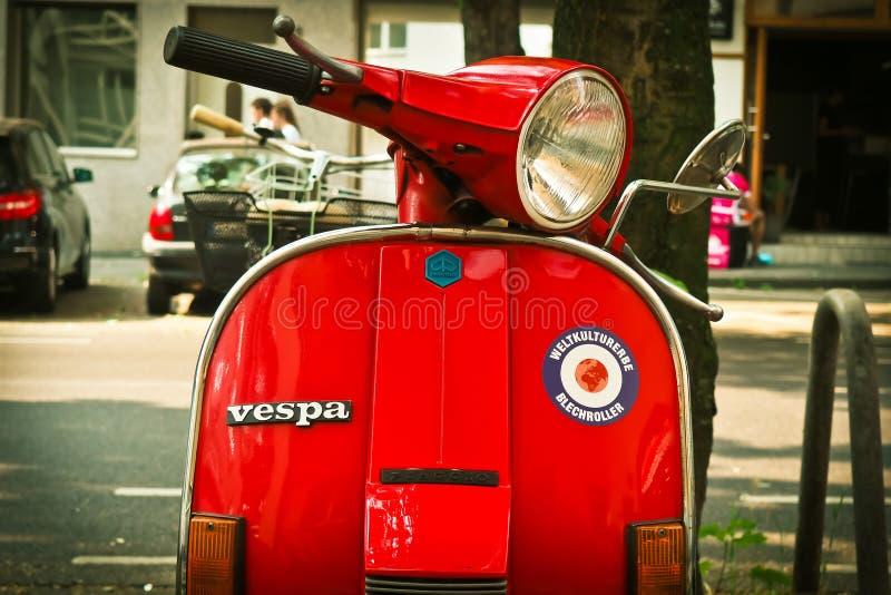 Motorisk sparkcykel för röd Vespa som parkeras nära träd under dag royaltyfri foto