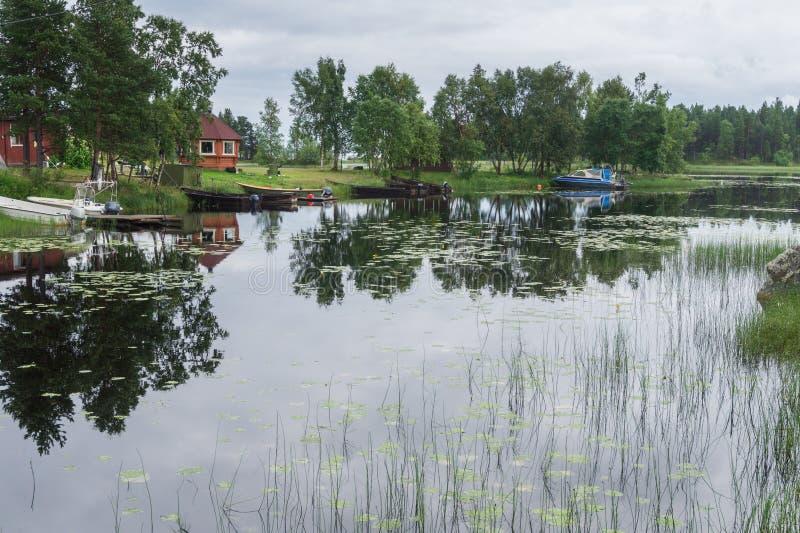 Motoriska fartyg och ett litet hus på kusten av sjön royaltyfri fotografi