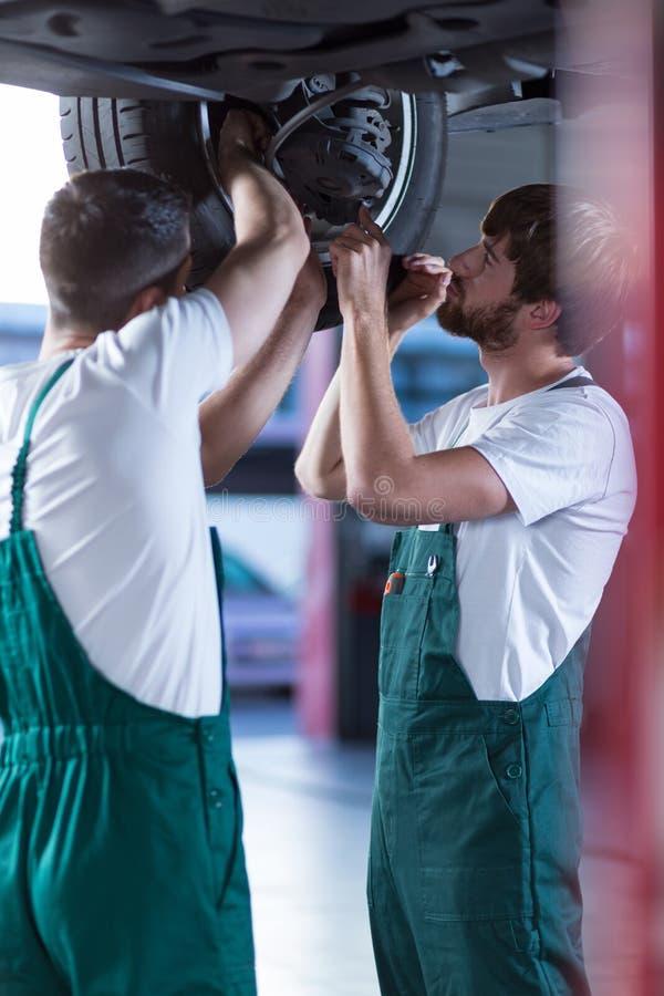 Motoriska mekaniker som arbetar i garage royaltyfria foton