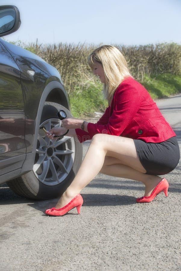 Motorist checking tire pressure of a car stock photo