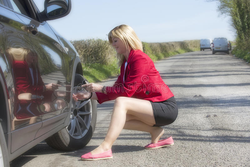 Motorist checking tire pressure of a car royalty free stock photos