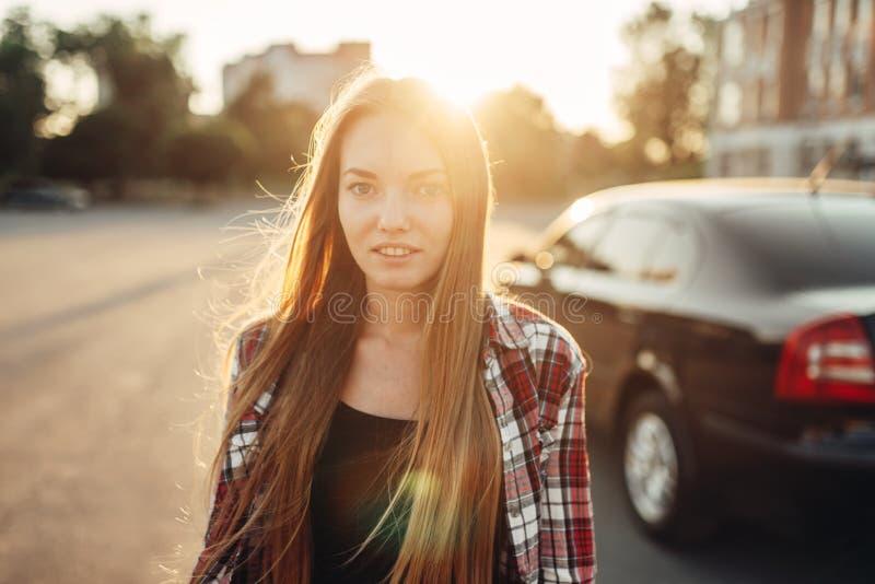 Motorista alegre novo da mulher que levanta contra um carro foto de stock royalty free