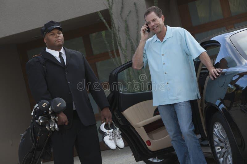 Motorista com o proprietário que está pelo carro foto de stock