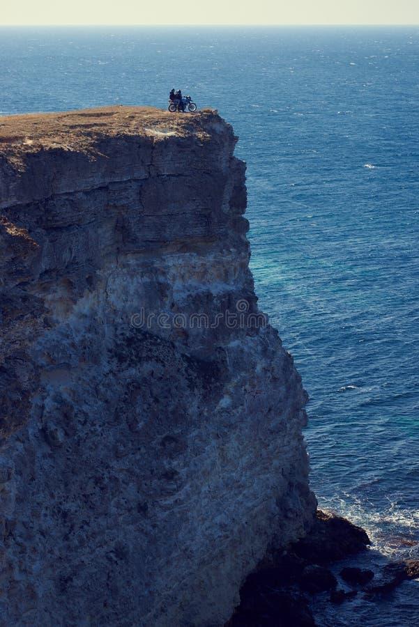 Motorista con la muchacha en el acantilado sobre el mar foto de archivo libre de regalías