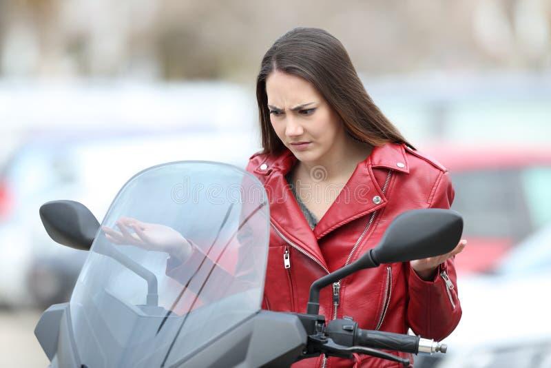 Motorista confuso que mira la moto analizada foto de archivo