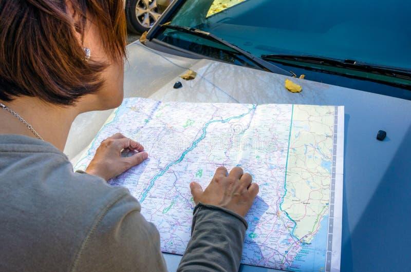 Motorista Consulting da mulher um mapa de estradas fotos de stock