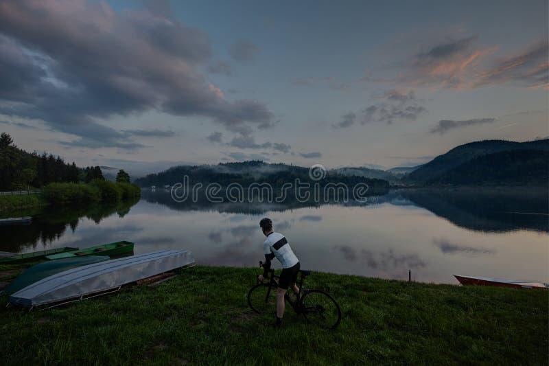 motorista da bicicleta da estrada que olha ao lago bonito com nuvens e reflexão foto de stock royalty free