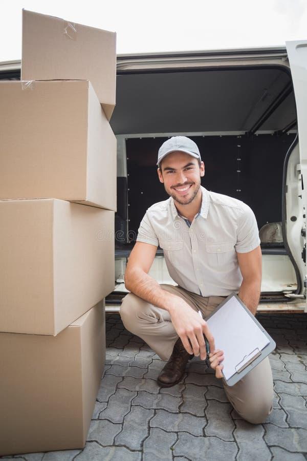 Motorista da entrega que sorri na câmera com a pilha dos pacotes imagens de stock