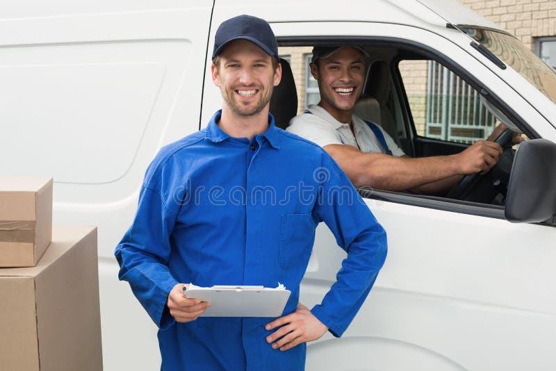 Motorista da entrega que verifica sua lista na prancheta com o cliente fotos de stock royalty free