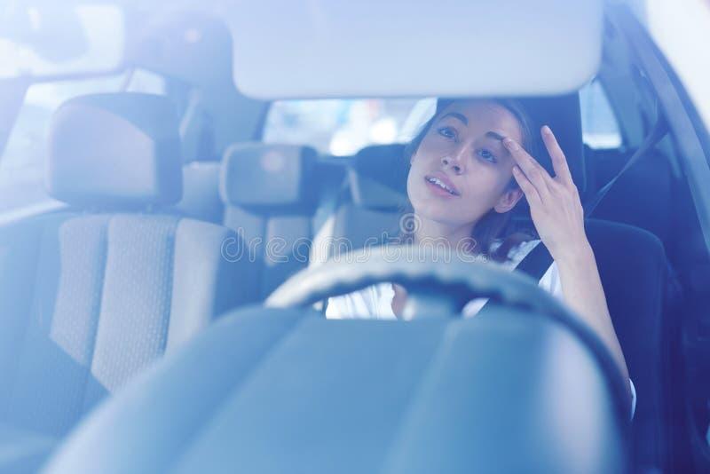 Motorista da mulher que olha o espelho retrovisor e que corrige o penteado e a composição ao conduzir o carro imagens de stock royalty free