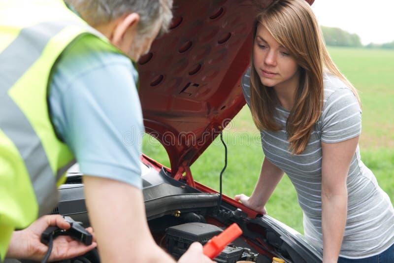 Motorista de la hembra de Helping Broken Down del mecánico imágenes de archivo libres de regalías