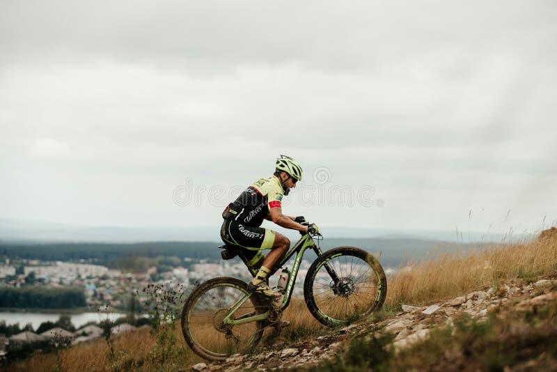 motorista de la montaña del ciclista del atleta que monta cuesta arriba imagenes de archivo