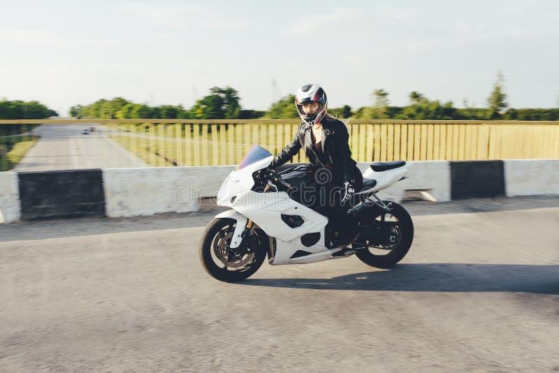 Motorista de la mujer que conduce una moto en un camino fotos de archivo libres de regalías
