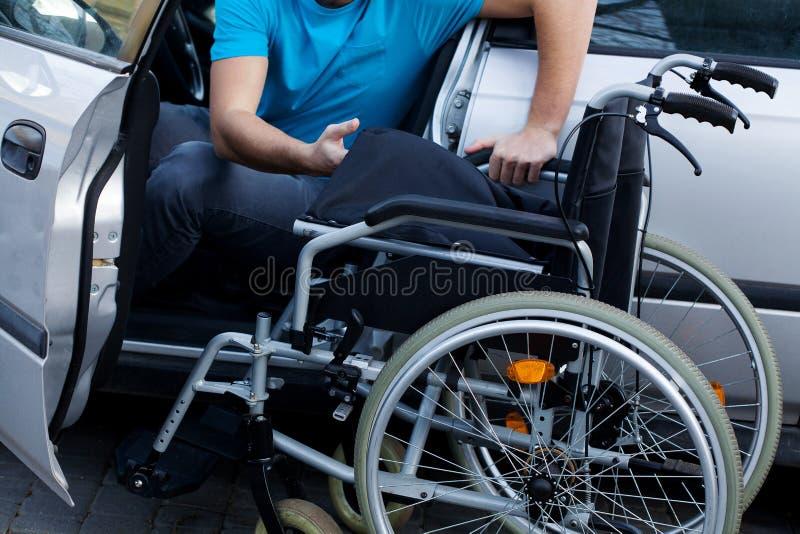 Motorista deficiente que consiste sua cadeira de rodas imagem de stock