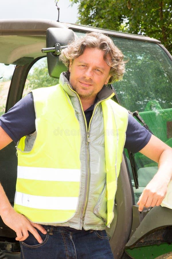 motorista do homem do construtor com o caminhão de forquilha do elevador na construção da construção fotografia de stock